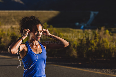 Buy stock photo Cropped shot of a young woman wearing earphones while out for a run