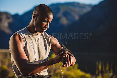 Buy stock photo Cropped shot of a man checking his wristwatch while out for a run