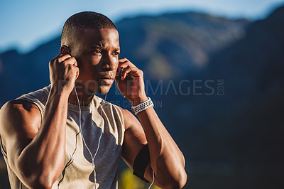 Buy stock photo Cropped shot of a sporty young man wearing earphones while out for a run