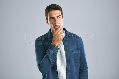 Buy stock photo Cropped shot of a handsome man looking thoughtful against a grey background