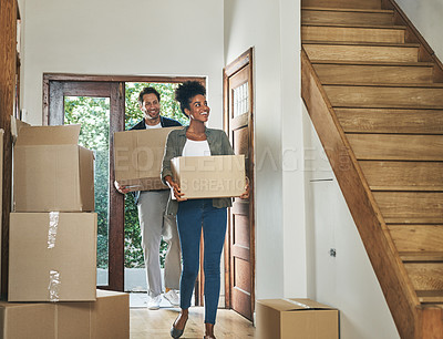 Buy stock photo Shot of an affectionate young couple smiling while carrying boxes into their new home
