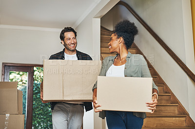 Buy stock photo Cropped shot of an affectionate young couple smiling at each other while carrying boxes into their new home