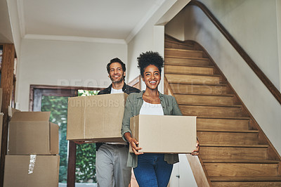 Buy stock photo Cropped shot of an affectionate young couple smiling while carrying boxes into their new home