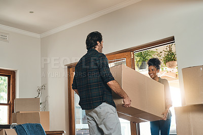 Buy stock photo Cropped shot of an affectionate young couple assisting each other to carry a box into their new home
