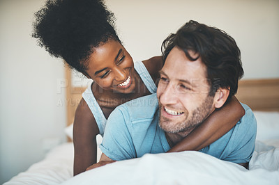 Buy stock photo Shot of an affectionate young woman embracing her husband while relaxing on their bed at home