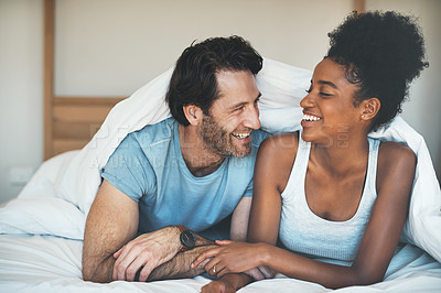 Buy stock photo Shot of an affectionate young couple laughing together while relaxing under their blanket in their bedroom