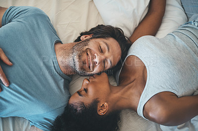 Buy stock photo High angle shot of an affectionate young woman kissing her husband on his cheek while lying on their bed at home