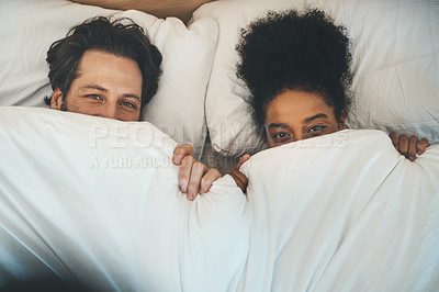 Buy stock photo High angle portrait of an affectionate young couple playfully covering themselves with a blanket in their bedroom at home