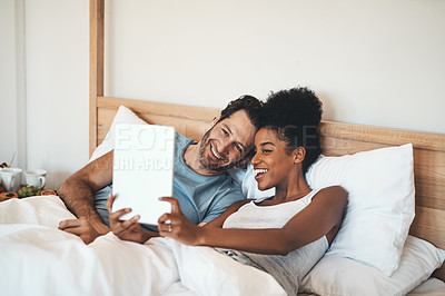 Buy stock photo Cropped shot of an affectionate young couple video calling using a digital tablet in bed in the morning