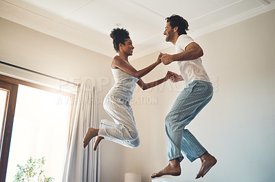 Buy stock photo Full length shot of an affectionate young couple jumping playfully on their bed at home