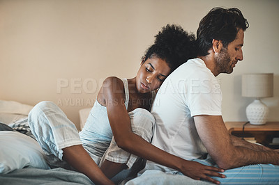 Buy stock photo Cropped shot of an affectionate young woman leaning on her husband's back after a fight in their bedroom at home