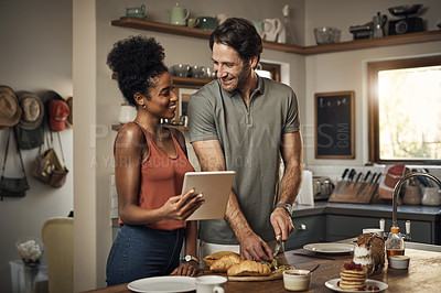 Buy stock photo Cropped shot of an affectionate young couple using a digital tablet while cooking together in their kitchen at home