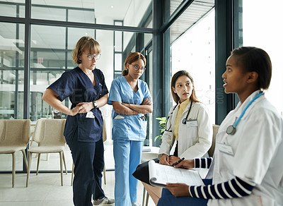 Buy stock photo Shot of a team of young doctors having a discussion in a modern hospital