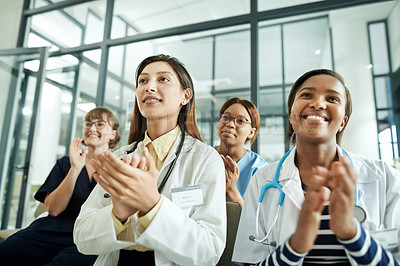 Buy stock photo Shot of a group of young doctors clapping during a conference in a modern hospital