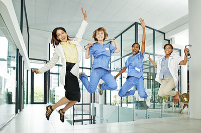 Buy stock photo Shot of a group of young doctors jumping enthusiastically in a modern hospital