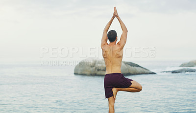 Buy stock photo Rearview shot of an unrecognizable man standing and doing yoga alone by the ocean during an overcast day