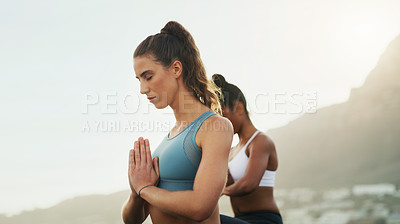 Buy stock photo Cropped shot of two attractive young women sitting and meditating together on the beach during an overcast day