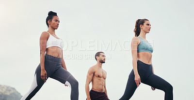 Buy stock photo Cropped shot of a group of young people standing and doing yoga while on the beach during an overcast day