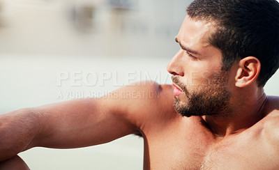 Buy stock photo Cropped shot of a handsome shirtless young sportsman sitting down while taking a break after a workout outdoors