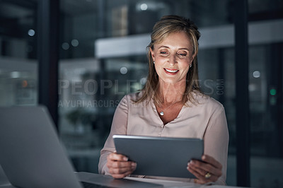 Buy stock photo Shot of a mature businesswoman using a digital tablet in an office at night