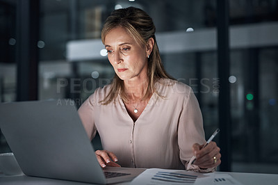 Buy stock photo Shot of a mature businesswoman using a laptop while writing notes in an office at night