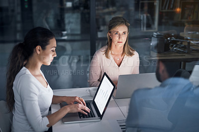 Buy stock photo Shot of a group of businesspeople having a meeting in an office at night
