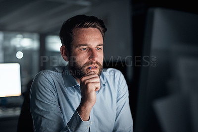 Buy stock photo Shot of a young businessman biting a pen while working on a computer in an office at night