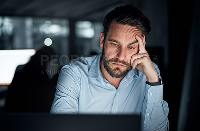 Buy stock photo Shot of a young businessman looking stressed out while working on a laptop in an office at night