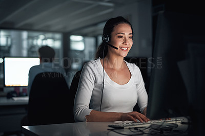 Buy stock photo Shot of a young call centre agent working on a computer in an office at night