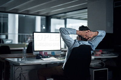Buy stock photo Rearview shot of a young businessman taking a break while working in an office at night