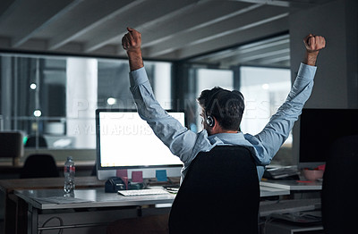 Buy stock photo Rearview shot of a young businessman stretching his arms while working in an office at night