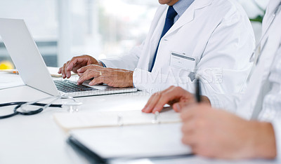 Buy stock photo Closeup shot of two unrecognisable doctors writing notes and using a laptop