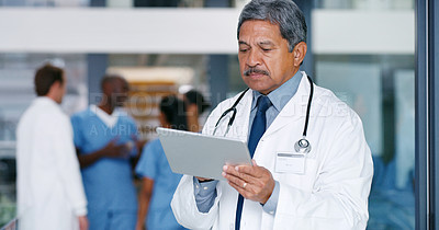 Buy stock photo Shot of a mature doctor using a digital tablet in a hospital