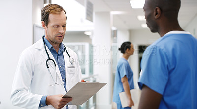 Buy stock photo Shot of a mature doctor talking to a colleague in a hospital