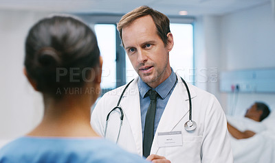Buy stock photo Shot of a mature doctor talking to a nurse in a hospital ward