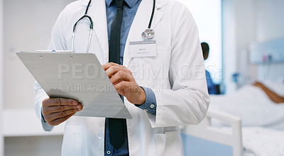 Buy stock photo Closeup shot of an unrecognisable doctor writing on a clipboard in a hospital ward