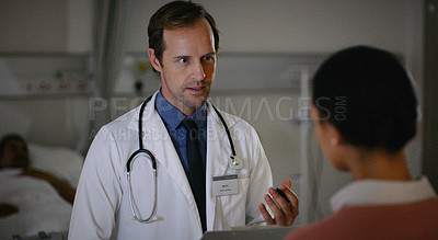 Buy stock photo Shot of a doctor talking to a woman in a hospital ward