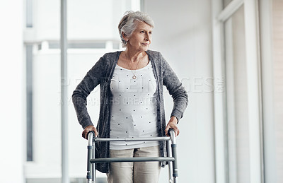 Buy stock photo Shot of a senior woman walking with the assistance of a walker