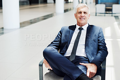 Buy stock photo Cropped portrait of a handsome mature businessman sitting and smiling while in the office during the day