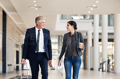Buy stock photo Cropped shot of two happy businesspeople walking through an airport terminal together during the day