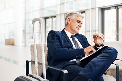 Buy stock photo Cropped shot of a handsome mature businessman looking at his watch while sitting in an airport terminal