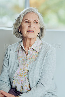 Buy stock photo Cropped shot of a contemplative senior woman sitting alone on a sofa in the living room of a nursing home
