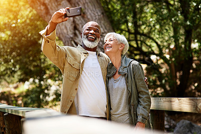 Buy stock photo Cropped shot of a happy senior couple taking a selfie while out hiking