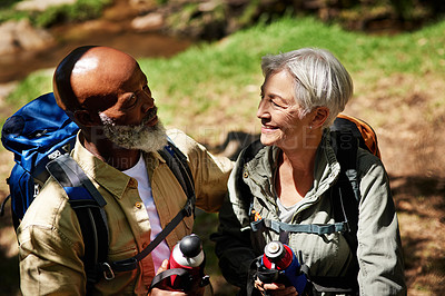 Buy stock photo Shot of a senior couple holding water bottles while taking a break from their hike
