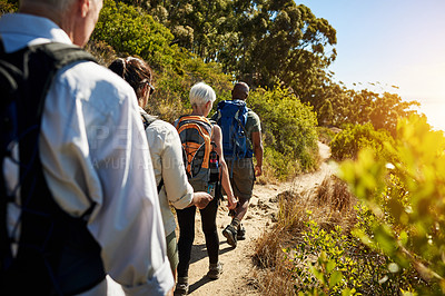 Buy stock photo Rearview shot a group of senior people hiking together in the mountains