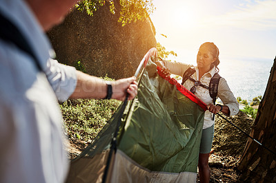 Buy stock photo Shot of a senior couple building a tent together while exploring in the mountains
