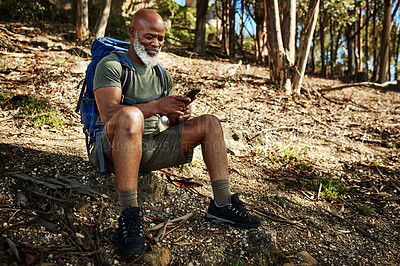 Buy stock photo Full length shot of a handsome senior man sitting down and using his cellphone while hiking outdoors