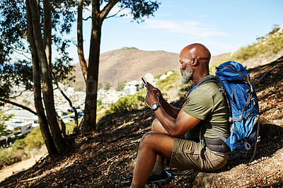 Buy stock photo Shot of a handsome senior man sitting down and using his cellphone while hiking outdoors