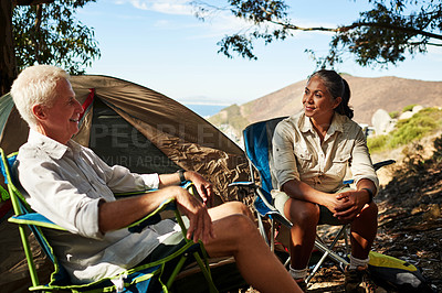 Buy stock photo Shot of a senior couple relaxing and sitting on camp chairs together while exploring out in the mountains