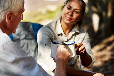 Buy stock photo Shot of a senior woman sharing a toast with her husband while exploring out in the mountains
